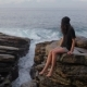 The Girl Is Seating on the Rocks Near the Ocean - VideoHive Item for Sale