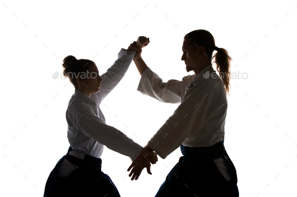 Man and woman fighting at Aikido training in martial arts school - Stock Photo - Images