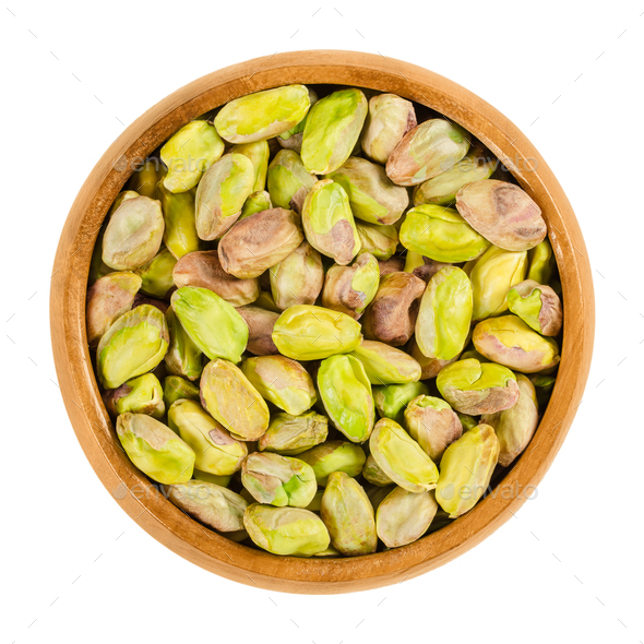 Shelled roasted pistachio kernels in wooden bowl over white - Stock Photo - Images