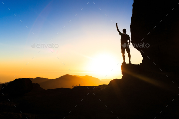 Man hiking climbing silhouette success in mountains sunset - Stock Photo - Images