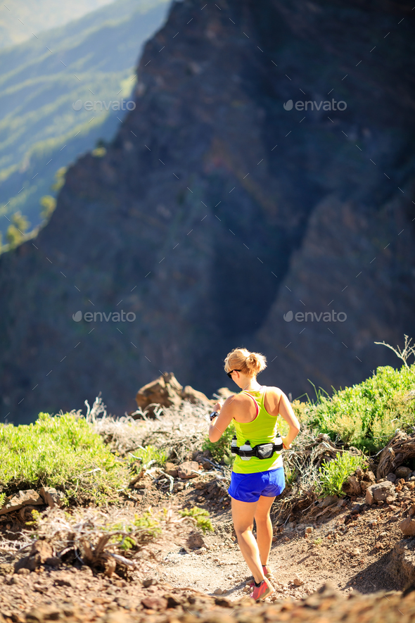 Woman walking running in rocky mountains on summer day - Stock Photo - Images