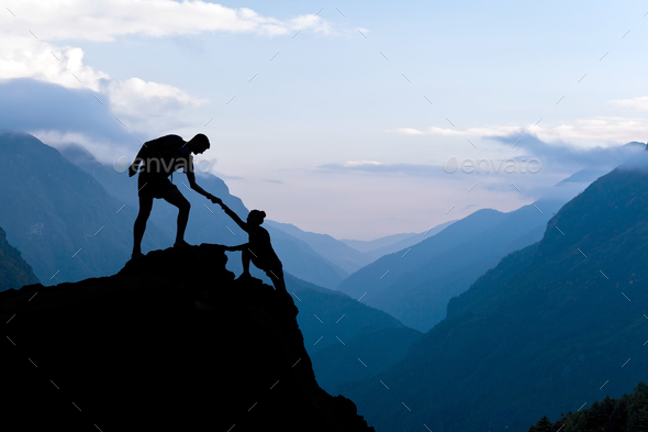 Teamwork couple climbing helping hand - Stock Photo - Images
