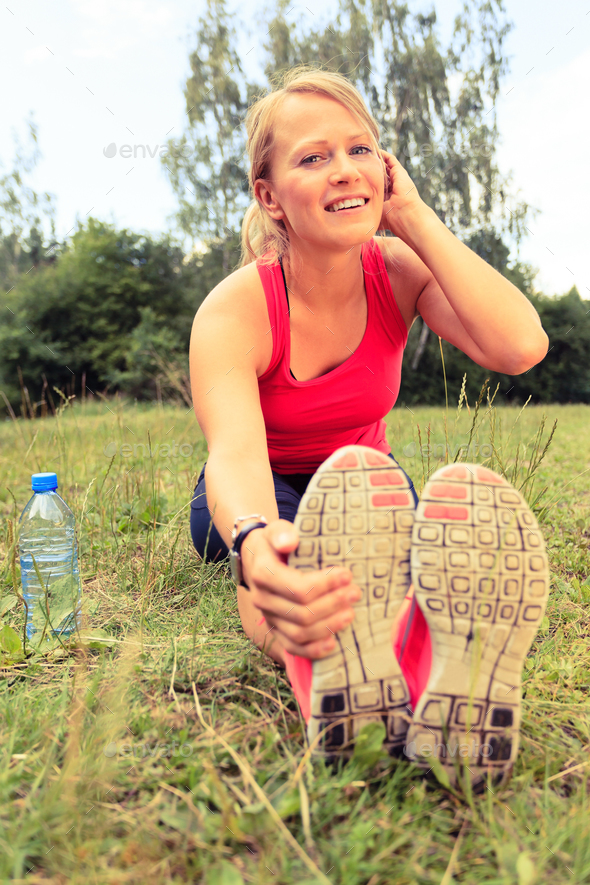 Woman runner exercising and stretching, summer nature outdoors - Stock Photo - Images