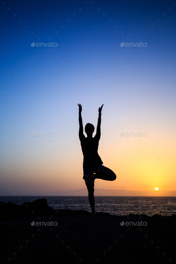 Woman exercising yoga sunset silhouette - Stock Photo - Images