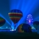 Hot Air Balloons Light Up the Night on the Field with People Walking Around Balloon Festival. Astana