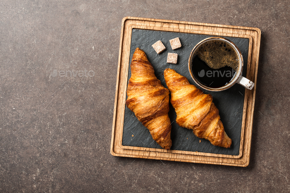 Morning black coffee with croissants on serving board - Stock Photo - Images