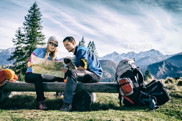 Couple hikers with map in mountains - Stock Photo - Images