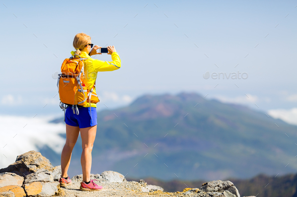 Woman hiker taking photos  in mountains - Stock Photo - Images