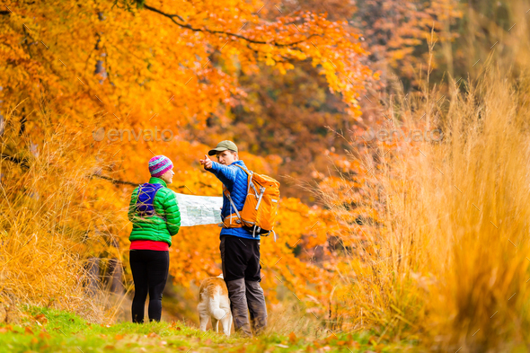 Couple hiking with map in autumn forest - Stock Photo - Images