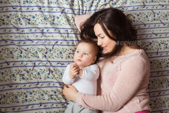 A Mother and baby child on a bed. - Stock Photo - Images