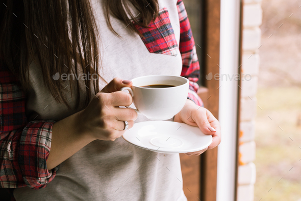 hands holding hot cup of coffee in morning - Stock Photo - Images