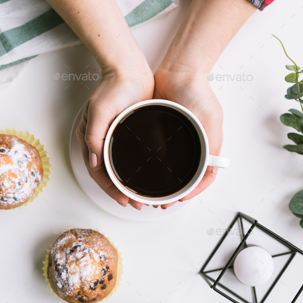 A cup of coffee in the hands and muffins on a white background and muffins - Stock Photo - Images