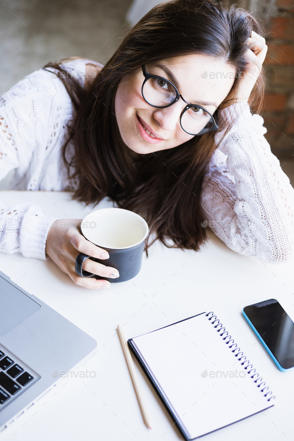 Beautiful woman in glasses sits holding a cup of coffee and using a laptop computer - Stock Photo - Images