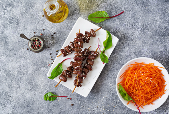 Chicken hearts in spicy sauce and carrot salad. Healthy food. Top view - Stock Photo - Images
