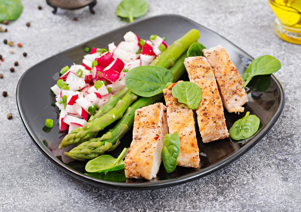 Chicken fillet cooked on a grill with a garnish of asparagus and radish salsa. - Stock Photo - Images