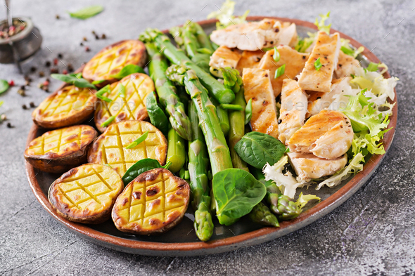 Chicken fillet cooked on a grill with a garnish of asparagus and baked potatoes.  - Stock Photo - Images