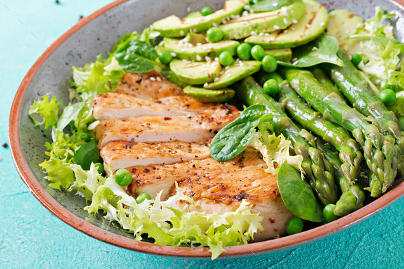 Chicken fillet cooked on a grill with a garnish of asparagus and grilled avokado - Stock Photo - Images