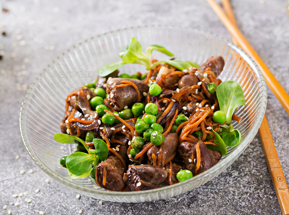 Chicken hearts with carrots, onions and green peas in Asian style. - Stock Photo - Images