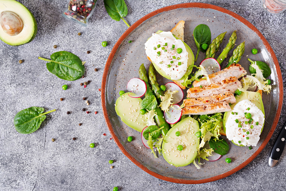 Healthy breakfast. Eggs poached on toast with avocado, asparagus and chicken fillet on grill. - Stock Photo - Images