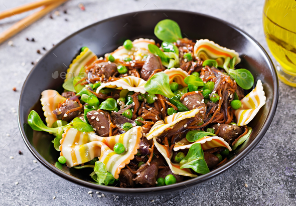 Chicken hearts with carrots in sweet and sour sauce with farfalle pasta. Healthy salad - Stock Photo - Images