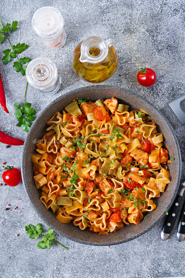 Pasta in the shape of hearts with chicken and tomatoes in tomato sauce. Top view - Stock Photo - Images