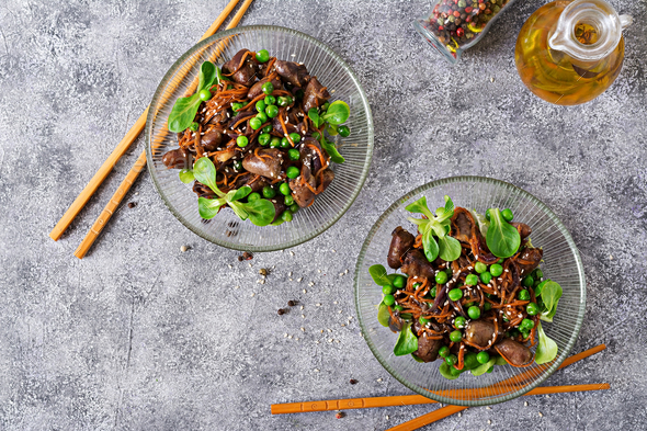 Chicken hearts with carrots, onions and green peas in Asian style. Top view - Stock Photo - Images