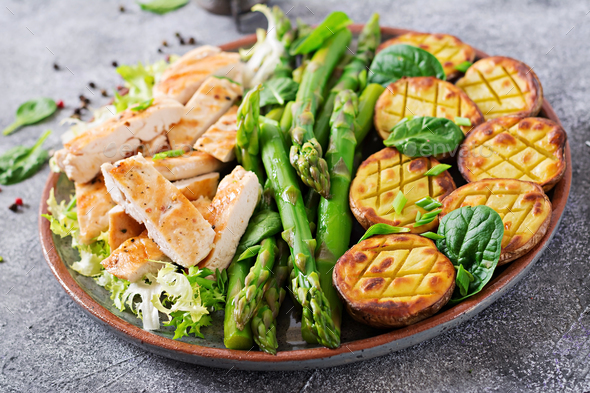 Chicken fillet cooked on a grill with a garnish of asparagus and baked potatoes - Stock Photo - Images