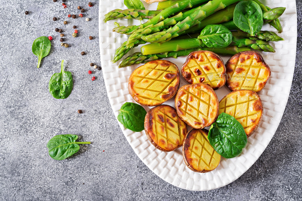 Halves of baked potatoes and asparagus. Dietary menu. Healthy food. - Stock Photo - Images