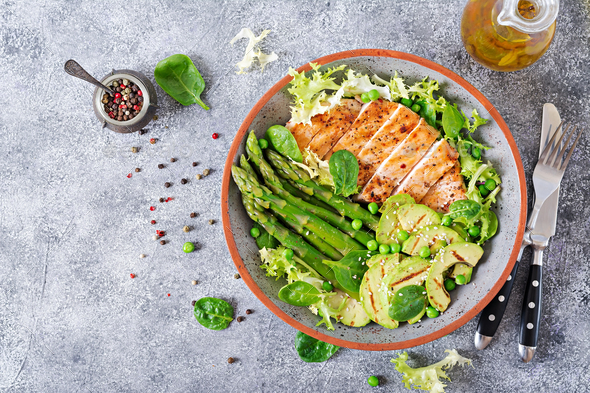 Chicken fillet cooked on a grill with a garnish of asparagus and grilled avokado. - Stock Photo - Images