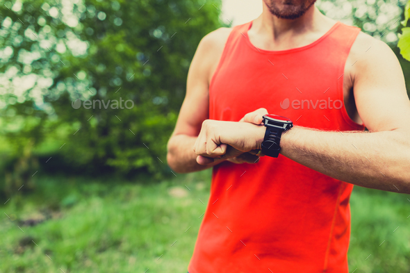 Runner looking at sport watch smartwatch - Stock Photo - Images