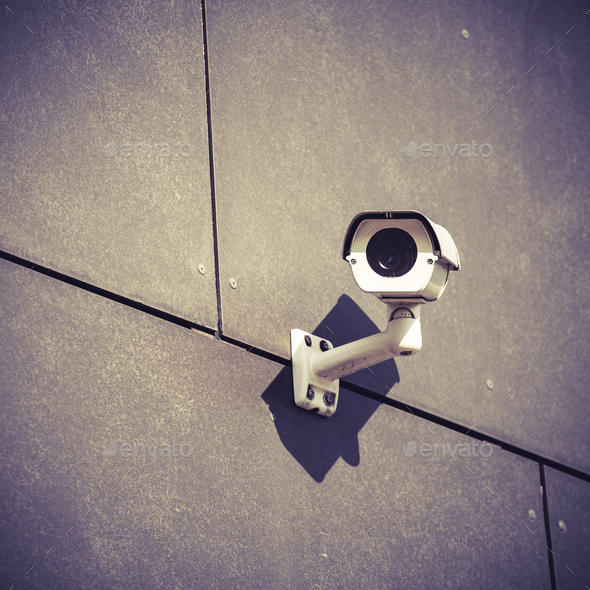 Security camera on gray office building wall - Stock Photo - Images