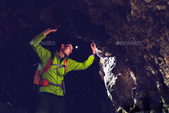 Man exploring underground dark cave tunnel - Stock Photo - Images