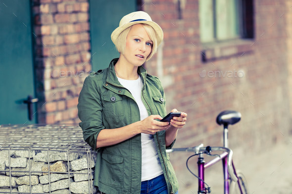 Hipster woman portrait with phone and bike - Stock Photo - Images