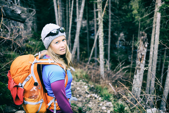 Woman hiking in winter cold dark winter forest - Stock Photo - Images