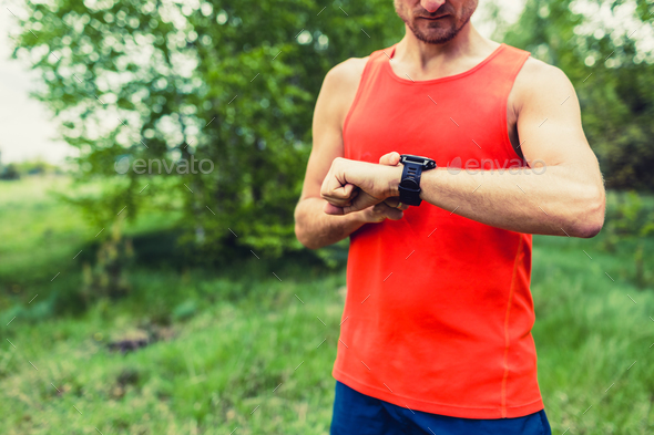 Runner looking at sport smart gps watch - Stock Photo - Images