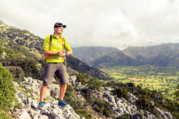 Hiking man checking direction in mountains - Stock Photo - Images