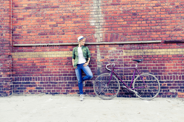 Young woman with vintage road bike in city - Stock Photo - Images