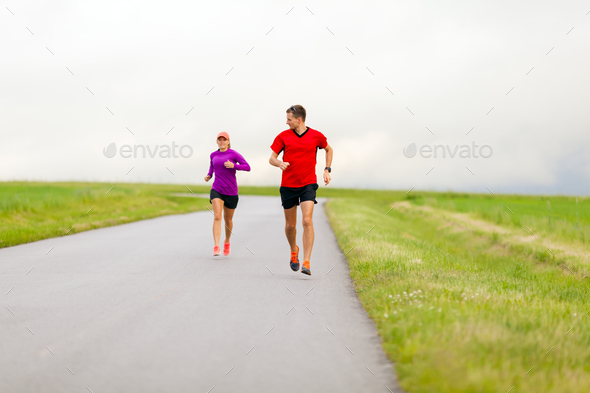 Couple running on country road - Stock Photo - Images