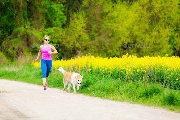 Woman running in summer park with dog - Stock Photo - Images