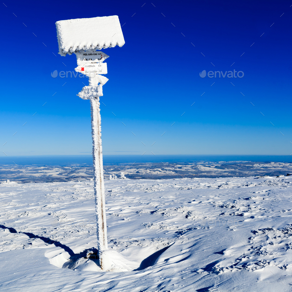 Sign and arrows in winter white mountains - Stock Photo - Images