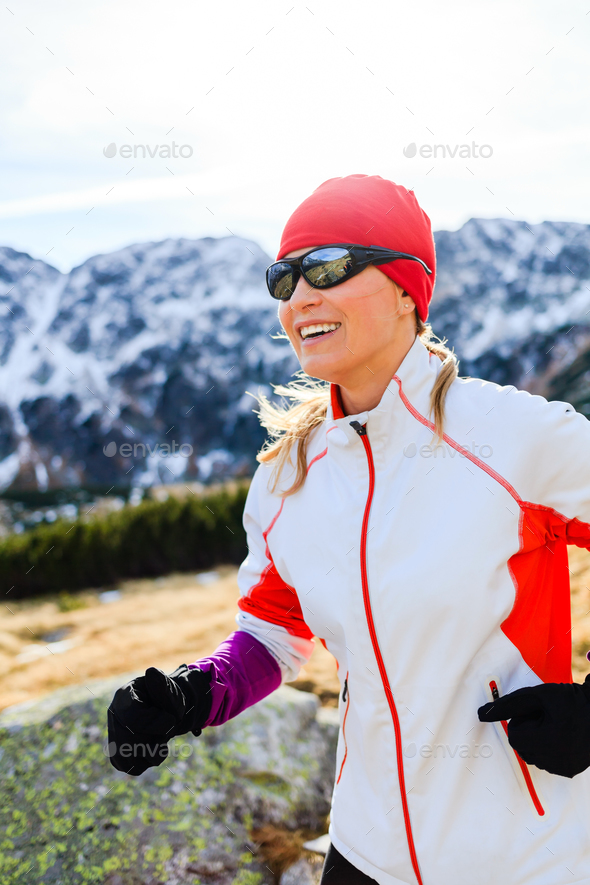 Young woman running in mountains on winter sunny day - Stock Photo - Images