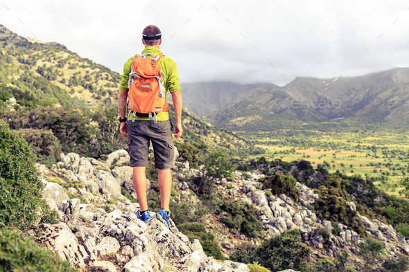 Hiking man looking at beautiful mountains - Stock Photo - Images