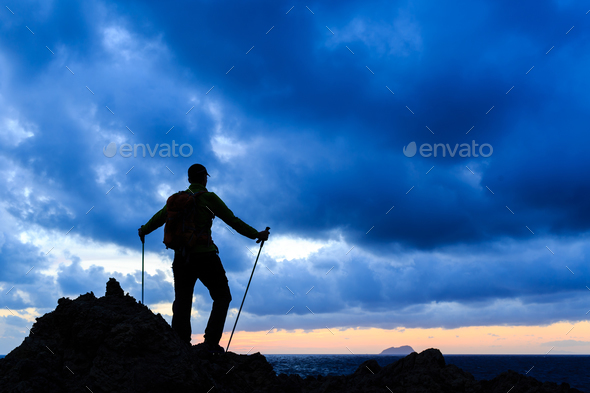Hiking silhouette backpacker looking at sunset ocean - Stock Photo - Images