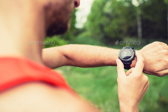 Runner looking checking sport watch - Stock Photo - Images