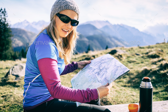Woman checking map hiking in mountains - Stock Photo - Images