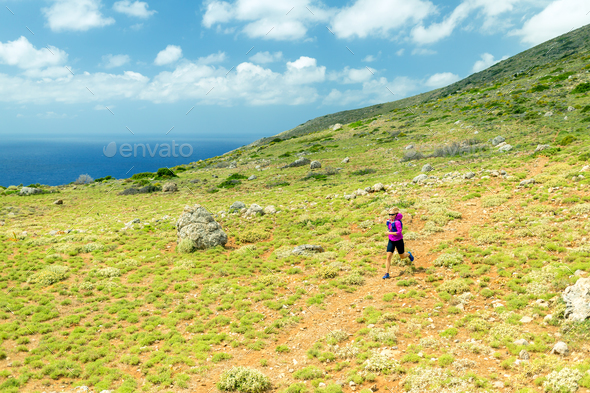 Happy woman trail running in beautiful mountains - Stock Photo - Images