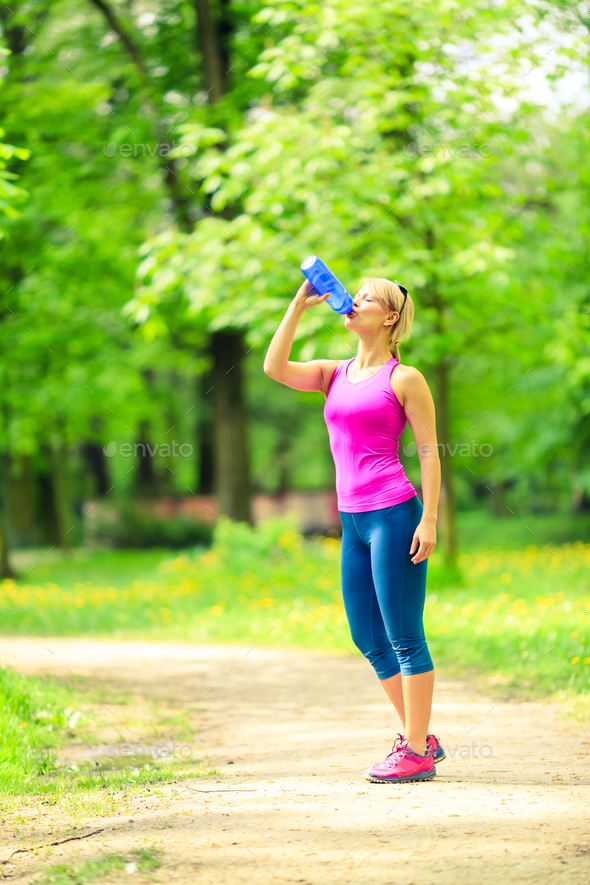 Woman runner drinking water on training - Stock Photo - Images