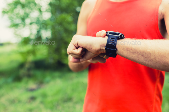 Man running and checking sport smart watch - Stock Photo - Images