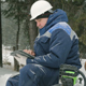 Worker With Tablet Computer on Big Pile of Logs in Winter Forest - VideoHive Item for Sale
