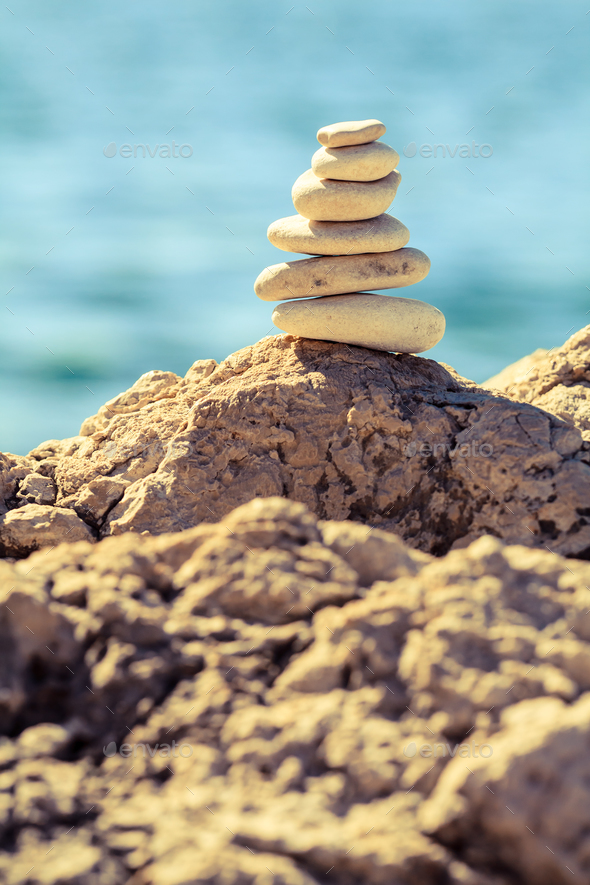 Stones balance at the beach, stack over blue sea - Stock Photo - Images